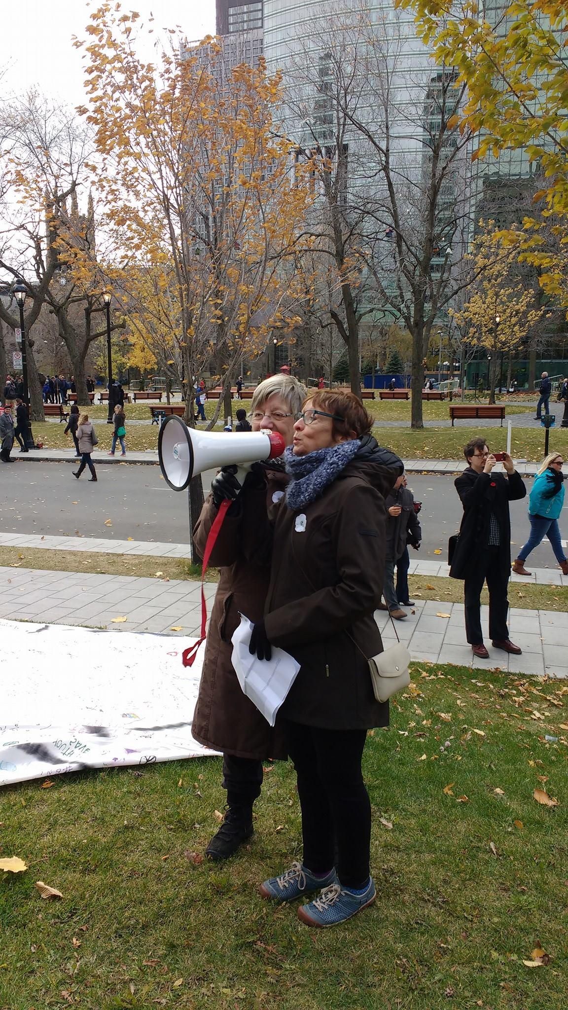 Vigile du Collectif Échec à la guerre le 11 novembre 2016. Ariane Émond, co-porte-parole de la campagne du coquelicot blanc 2016 prend la parole à la fin du rassemblement, en compagnie de Martine Éloy.  Crédit photo: Mercédez Roberge.